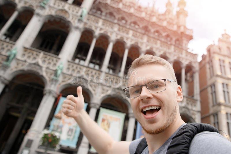 Estudiante feliz del hombre con la mochila que toma la foto del selfie en el cuadrado central Bruselas, Bélgica imagen de archivo