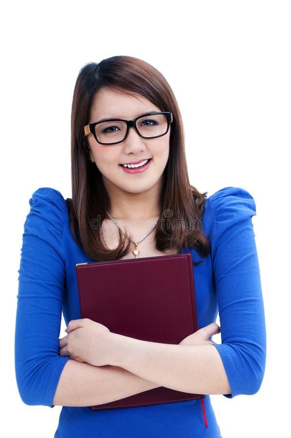 Estudiante feliz en las lentes que abrazan su libro fotos de archivo libres de regalías