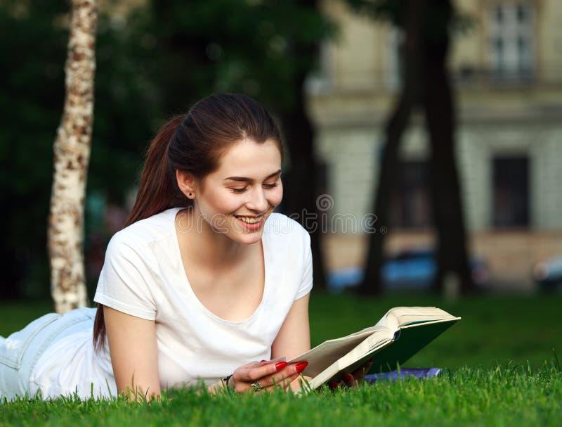 Estudiante feliz en parque de la ciudad que lee un libro imagen de archivo