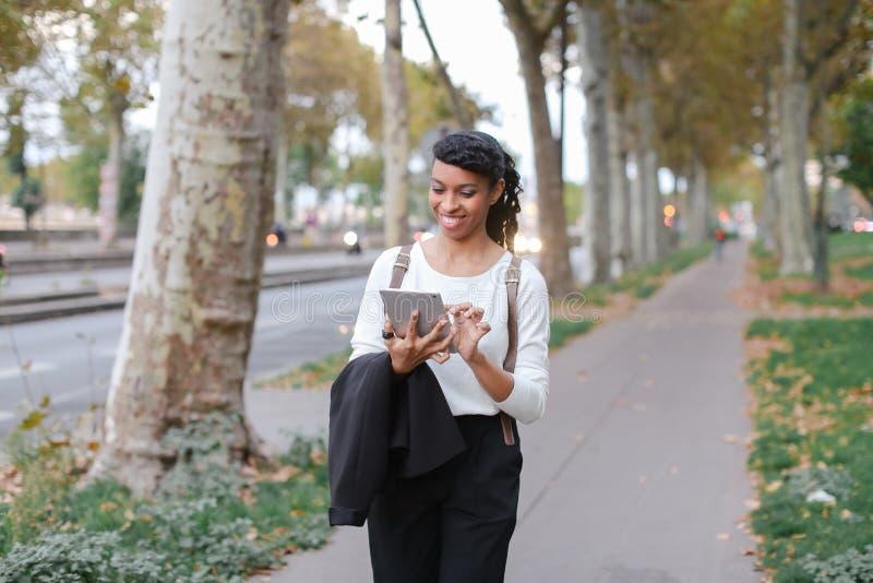 Estudiante feliz femenino negro que usa la tableta y caminando en la calle con los árboles fotografía de archivo