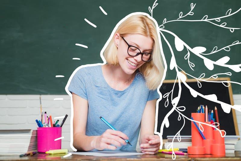 Estudiante feliz joven Estudiante que estudia en la sala de clase Estudiante casual feliz con el fondo excesivo de la pizarra fotos de archivo