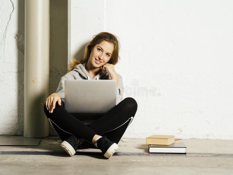 Estudiante feliz joven que trabaja en su ordenador portátil en vestíbulo de la escuela imágenes de archivo libres de regalías