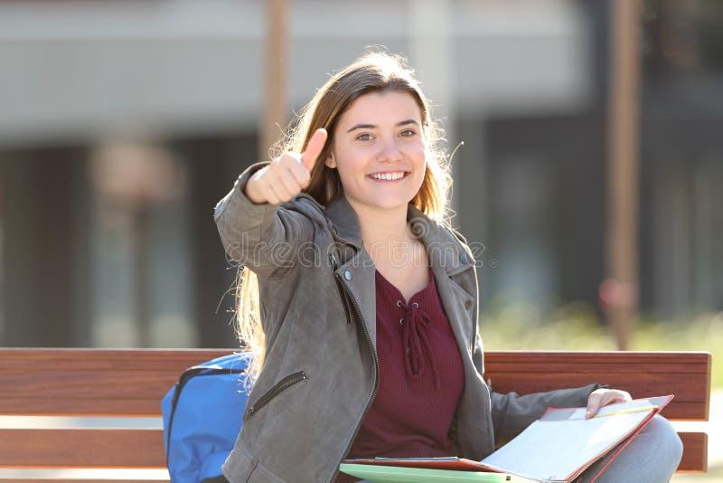 Estudiante feliz que gesticula el pulgar encima de sentarse en un banco imágenes de archivo libres de regalías