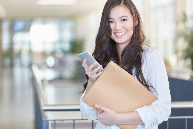 Estudiante feliz que sostiene smartphone y el cuaderno imagen de archivo libre de regalías