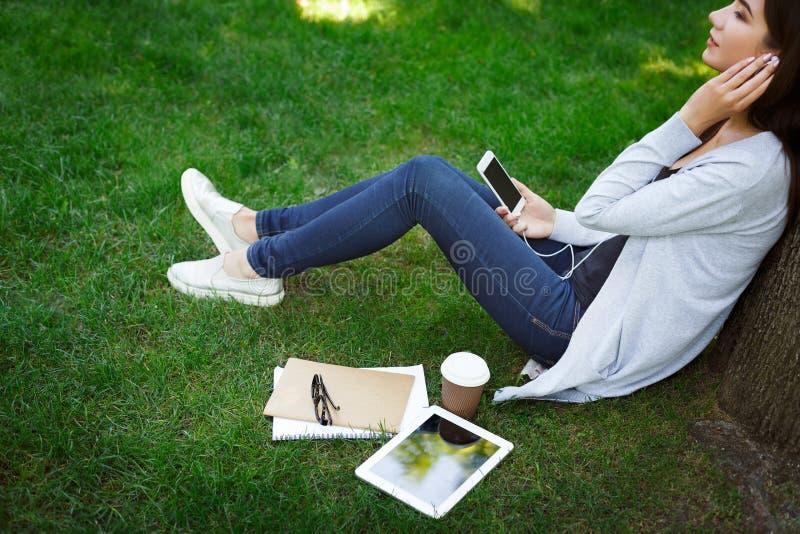 Estudiante femenino joven sonriente del asiático las TIC en auriculares El escuchar la música y café de consumición en el parque fotografía de archivo