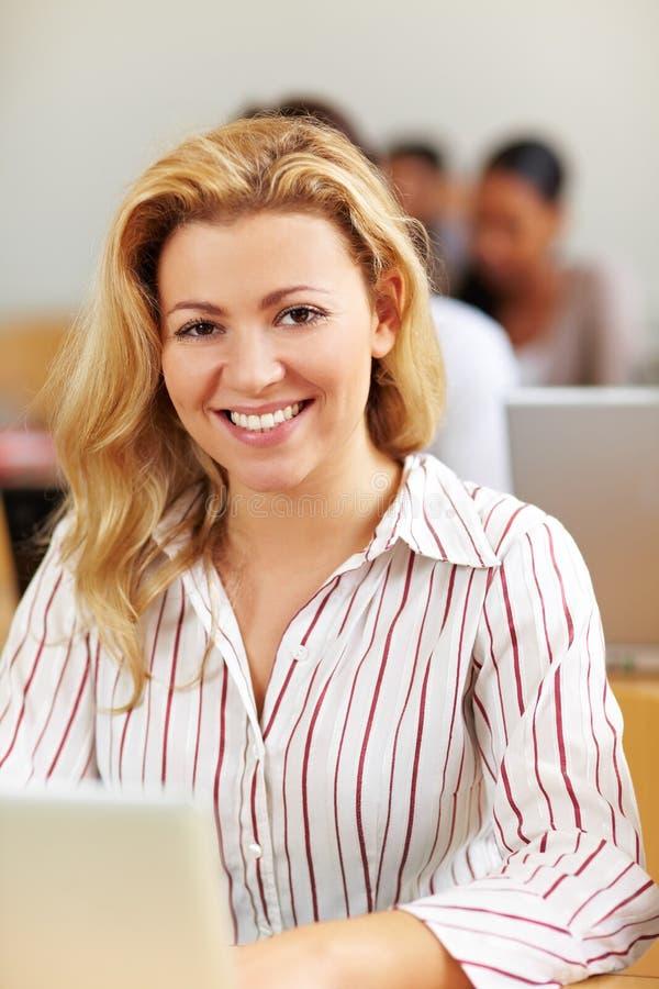 Estudiante femenino sonriente en la computadora portátil fotografía de archivo