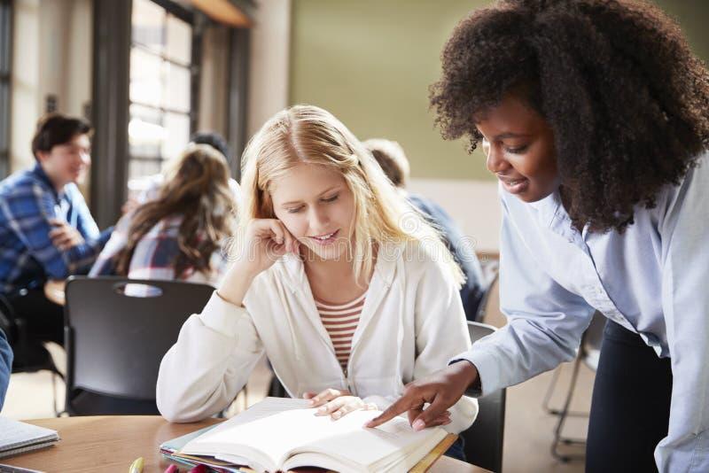 Estudiante femenino With Teacher Working de la High School secundaria en el escritorio foto de archivo libre de regalías
