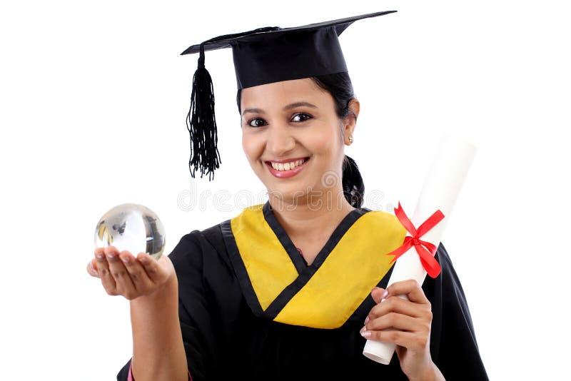 Estudiante graduado femenino que sostiene un globo de cristal foto de archivo