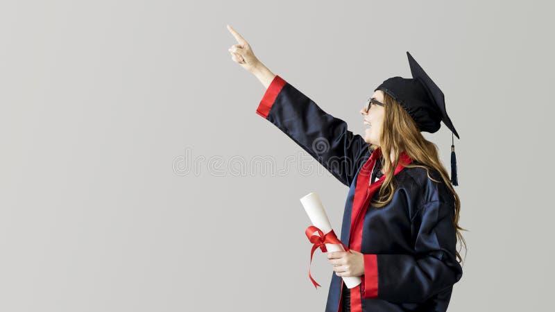 Estudiante graduado joven que muestra lejos en fondo gris imágenes de archivo libres de regalías