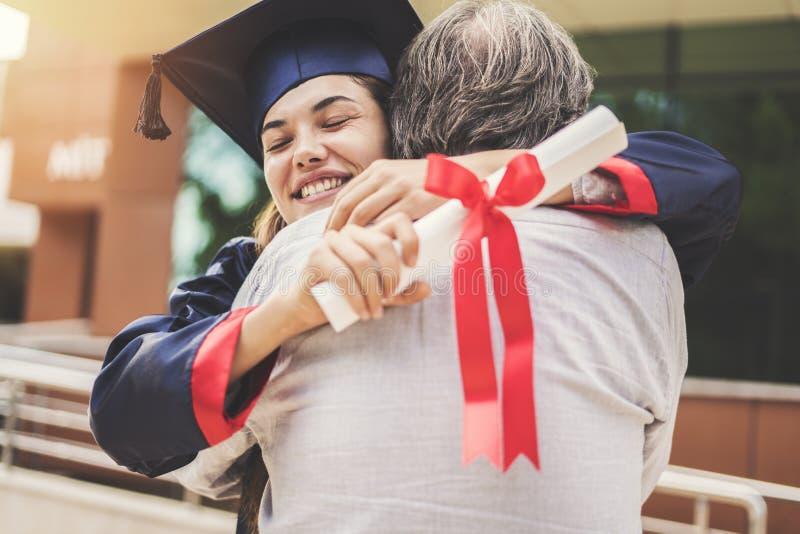 Estudiante graduado que abraza a su padre imágenes de archivo libres de regalías