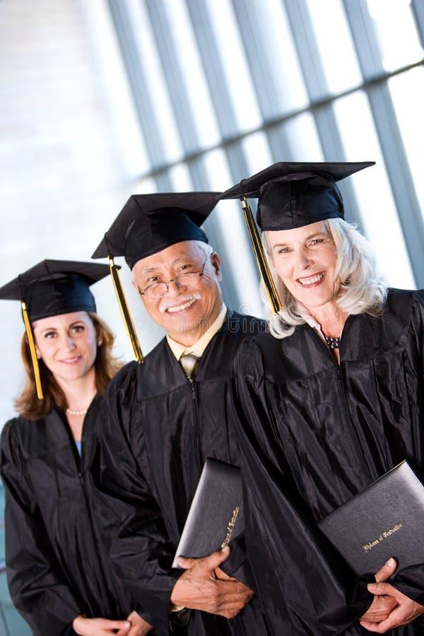 Estudiante: Grupo de estudiantes adultos sonrientes en la graduación imagenes de archivo