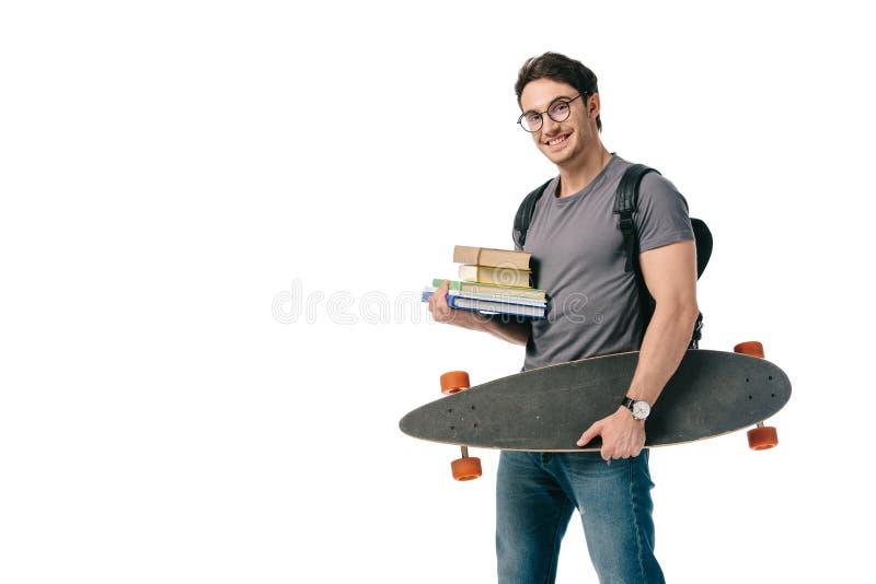 estudiante hermoso feliz que sostiene los libros y el patín imagen de archivo