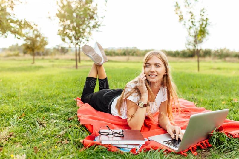 Estudiante hermoso joven con los vidrios, hablando en el teléfono, y fotografía de archivo