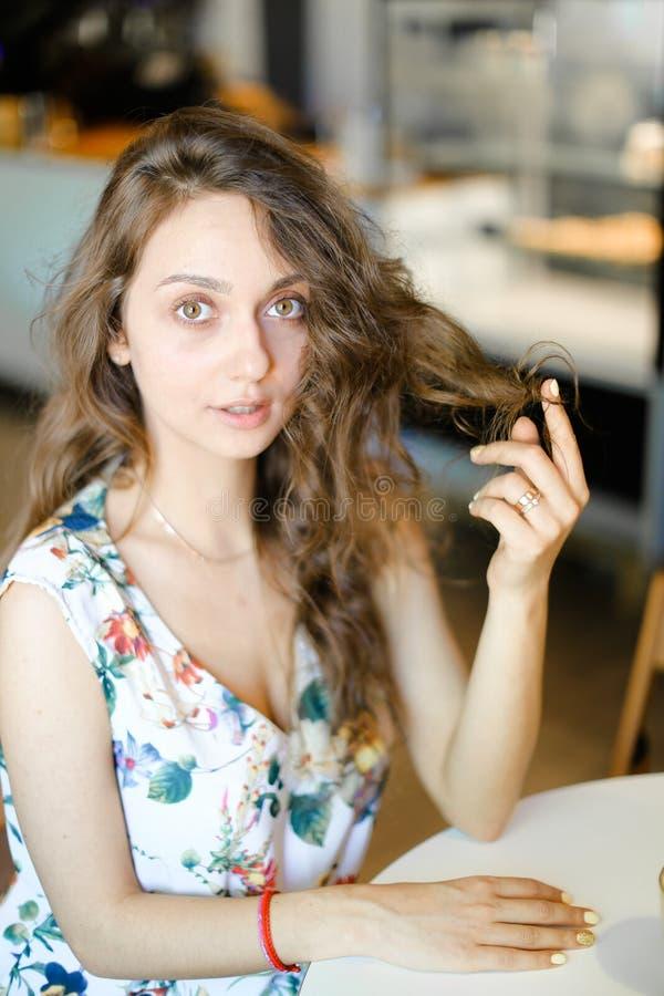 Estudiante hermoso joven que se sienta en el café y que toca el pelo rizado fotos de archivo libres de regalías
