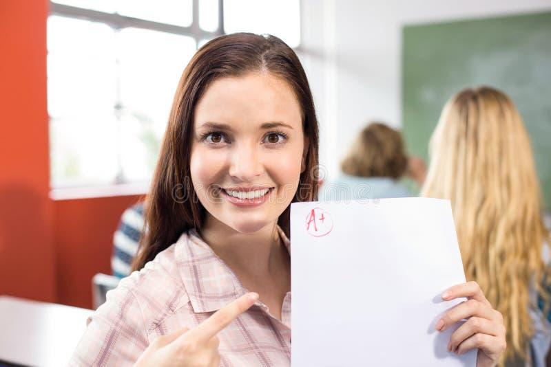 Estudiante hermoso que señala en el papel foto de archivo libre de regalías