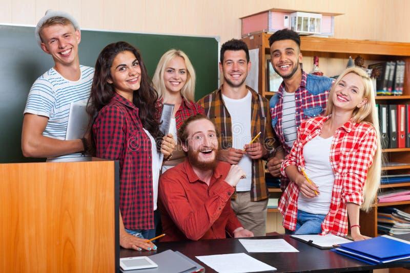 Estudiante High School Group que ríe con profesor Sitting At Desk, sala de clase sonriente de la universidad de la gente joven foto de archivo