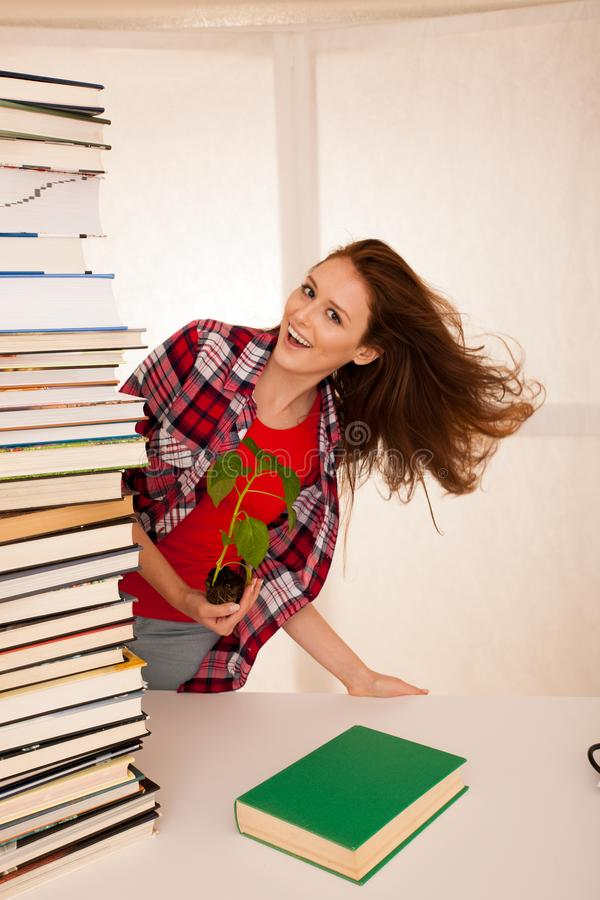Estudiante joven atractivo de la botánica con el seedlnng y los libros foto de archivo