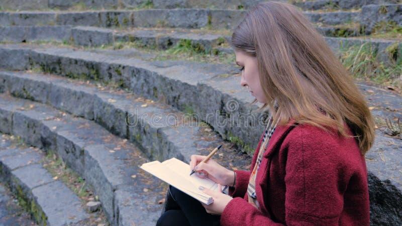 Estudiante joven atractivo que se prepara para las conferencias en universidad mientras que se sienta en las escaleras, escribien imagen de archivo