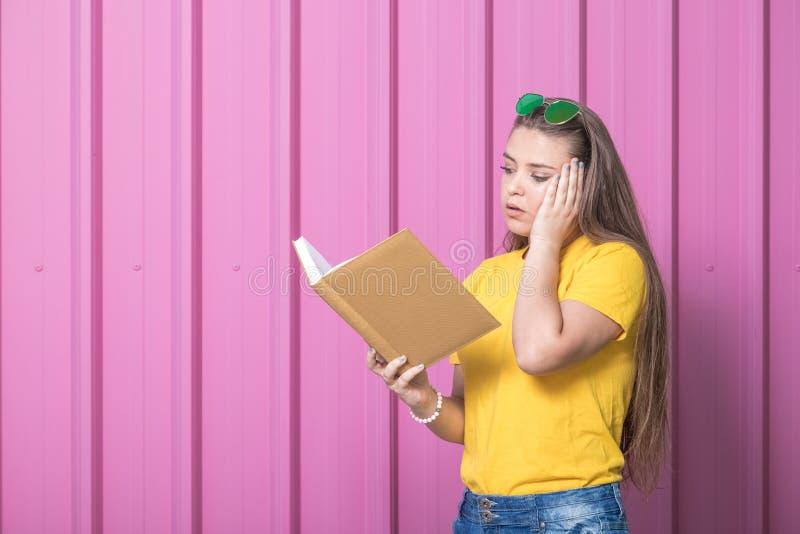 Estudiante joven bajo tensión que lee un libro contra la pared color de rosa foto de archivo