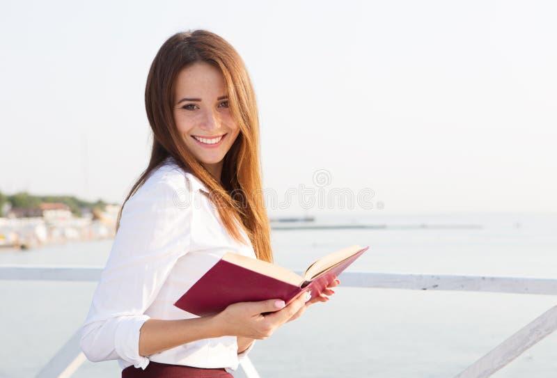 Estudiante joven con el libro en la playa foto de archivo libre de regalías