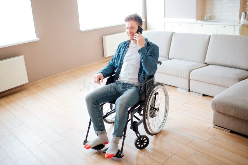 Estudiante joven con la incapacidad que se sienta en silla de ruedas y que habla en el teléfono Solamente en sitio vacío Indivi foto de archivo libre de regalías