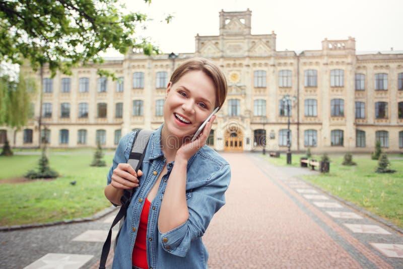 Estudiante joven con la mochila en hablar que camina del campus universitario en la risa del smartphone juguetona imagen de archivo