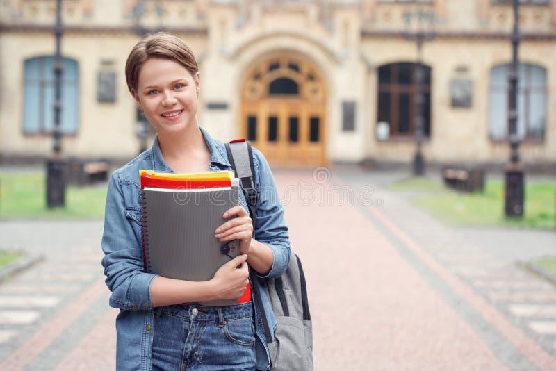 Estudiante joven con la mochila en la situación del campus universitario con los cuadernos que miran el positivo de la cámara fotografía de archivo