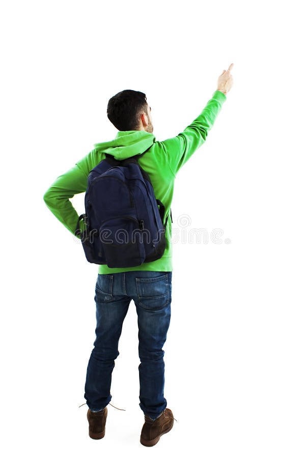 Estudiante joven con las mochilas que señala en la pared Visión posterior imagen de archivo