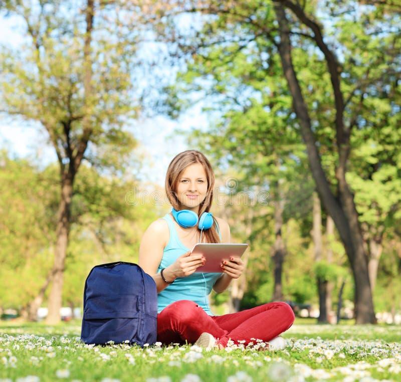 Estudiante joven con los auriculares y la tableta que se sientan en parque foto de archivo libre de regalías