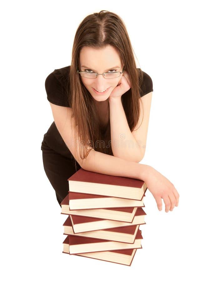 Estudiante joven con los vidrios y una pila de libros foto de archivo libre de regalías