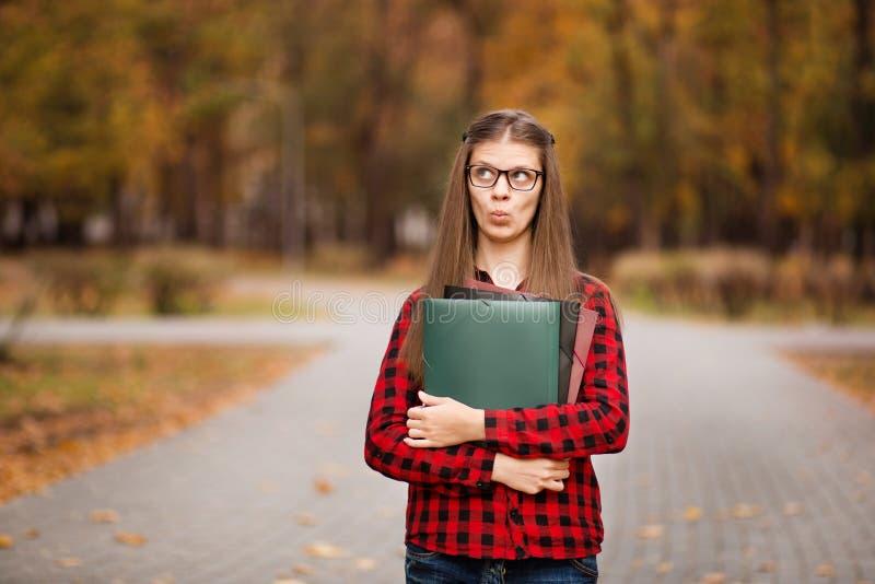 Estudiante joven con miradas sorprendidas de la cara fuera de la carpeta en camisa a cuadros roja Retrato de la mujer joven lista foto de archivo libre de regalías