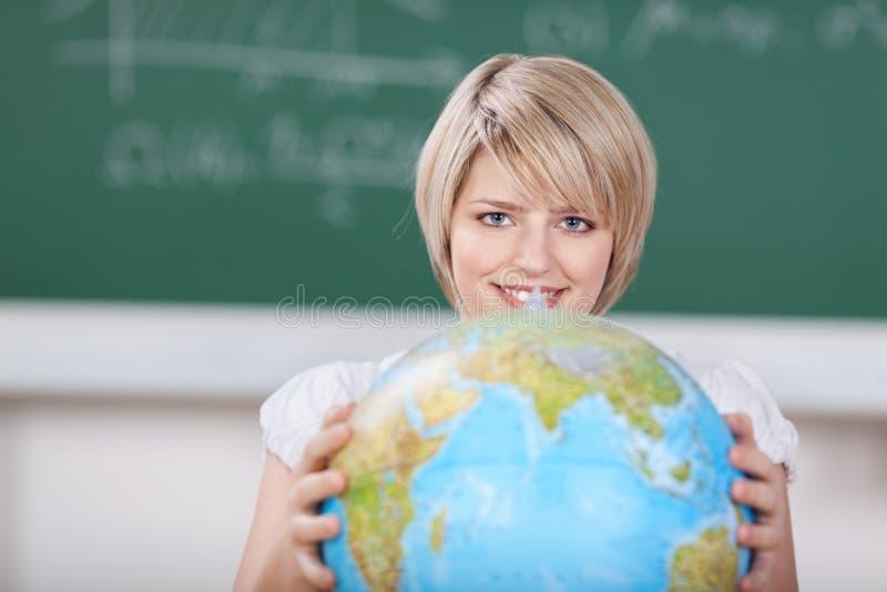 Estudiante joven con un globo del mundo imagenes de archivo