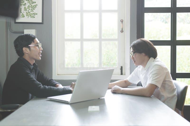 Estudiante joven de los pares que discute cosas y que trabaja en un proyecto mientras que se sienta en la escuela imagen de archivo