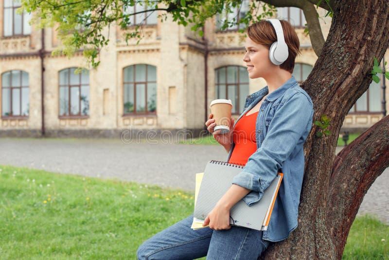 Estudiante joven en auriculares en el campus universitario que se inclina en árbol con los cuadernos que bebe la mirada de la m imagenes de archivo