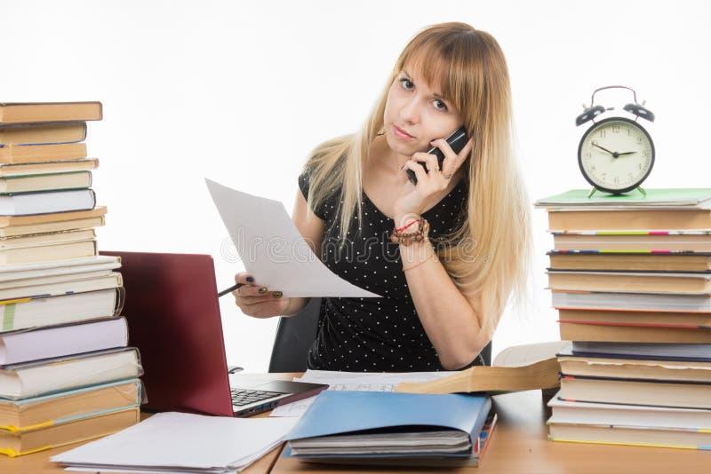 Estudiante joven en el teléfono que discute el proyecto ejecutado del curso imagen de archivo libre de regalías