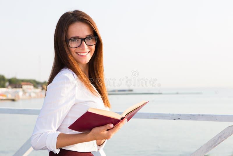 Estudiante joven en vidrios de lectura con el libro foto de archivo