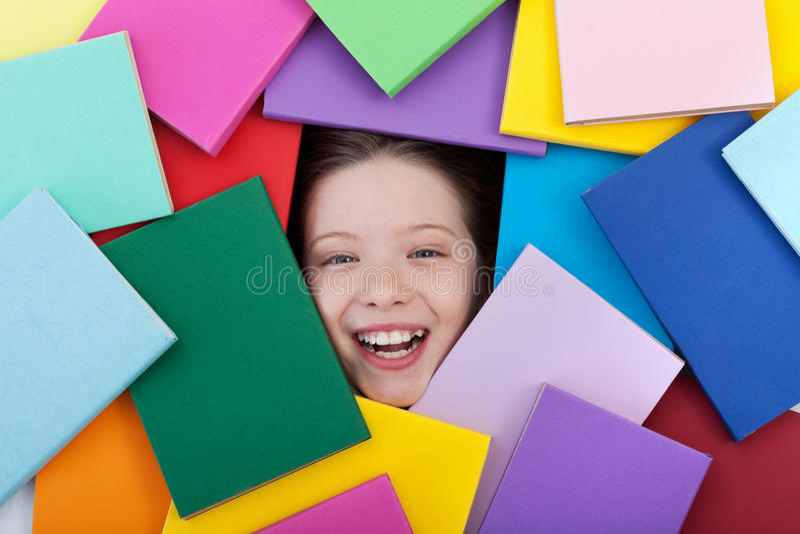 Estudiante joven feliz cubierto con los libros imagen de archivo libre de regalías