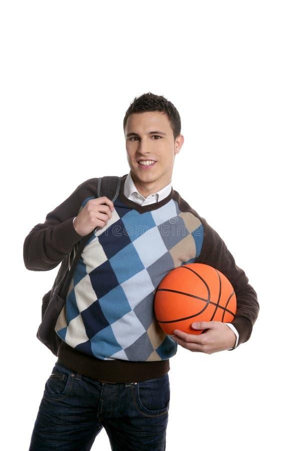 Estudiante joven feliz del muchacho con la bola del baloncesto foto de archivo libre de regalías