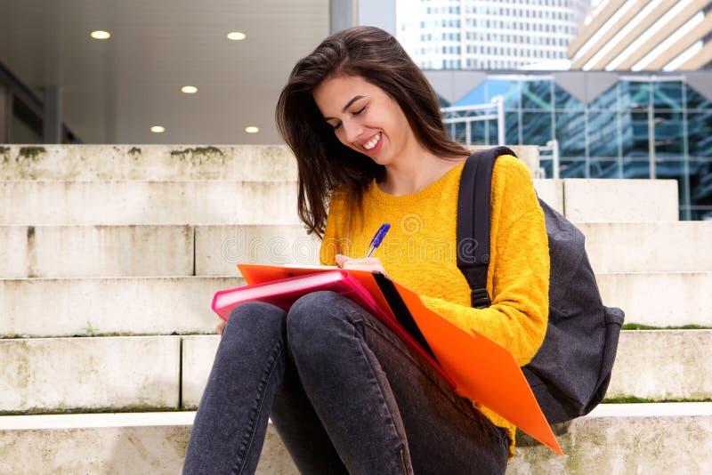 Estudiante joven feliz que toma notas sobre pasos imágenes de archivo libres de regalías