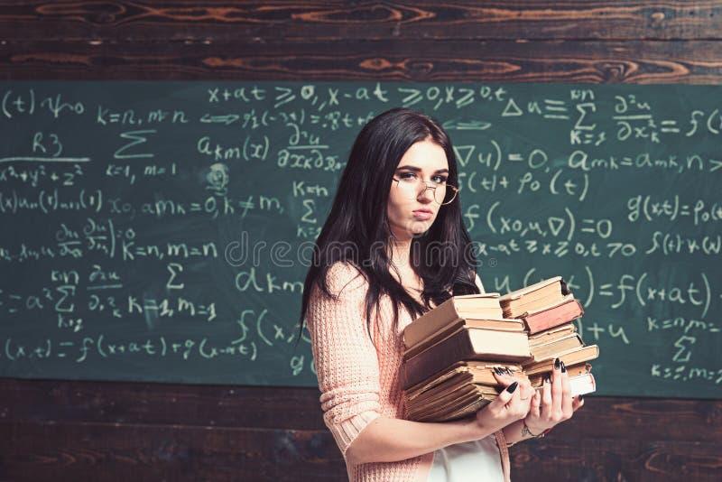 Estudiante joven femenino serio antes de ex?menes Muchacha morena en los vidrios que llevan dos pilas de libros pesados imágenes de archivo libres de regalías