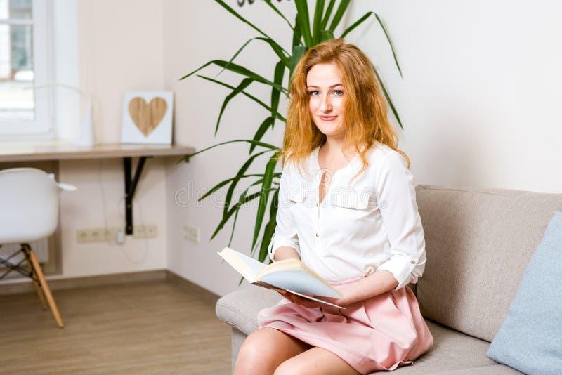 Estudiante joven hermoso con el pelo rojo largo en una falda y una camisa rosadas que lee un libro, llevando a cabo en su mano un foto de archivo libre de regalías