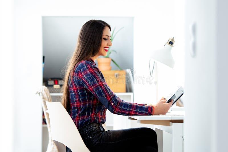 Estudiante joven hermoso que se sienta en su escritorio, estudiando foto de archivo
