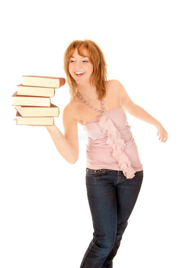 Estudiante joven que balancea una pila de libros foto de archivo libre de regalías