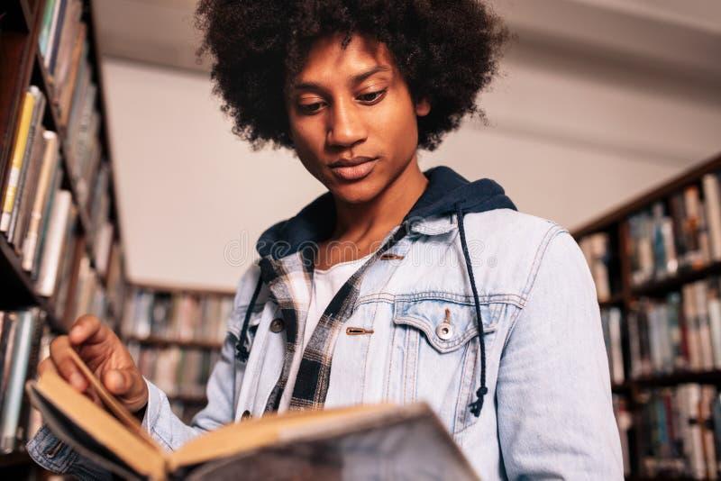 Estudiante joven que lee un libro en biblioteca imagen de archivo libre de regalías