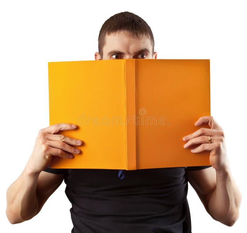 Estudiante joven que lee un libro espantoso foto de archivo