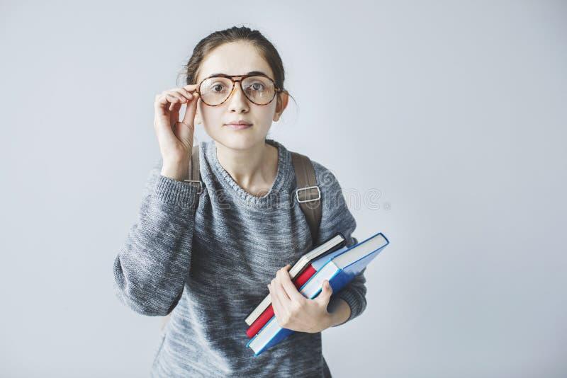 Estudiante joven que mira cuidadosamente y que sostiene los libros foto de archivo libre de regalías