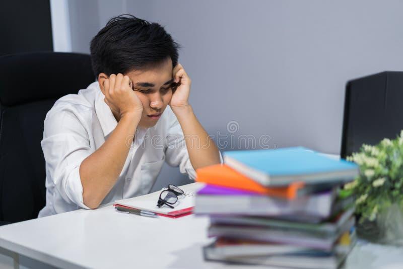 Estudiante joven que se sienta y que duerme en el escritorio con el libro y el ordenador portátil imagen de archivo libre de regalías