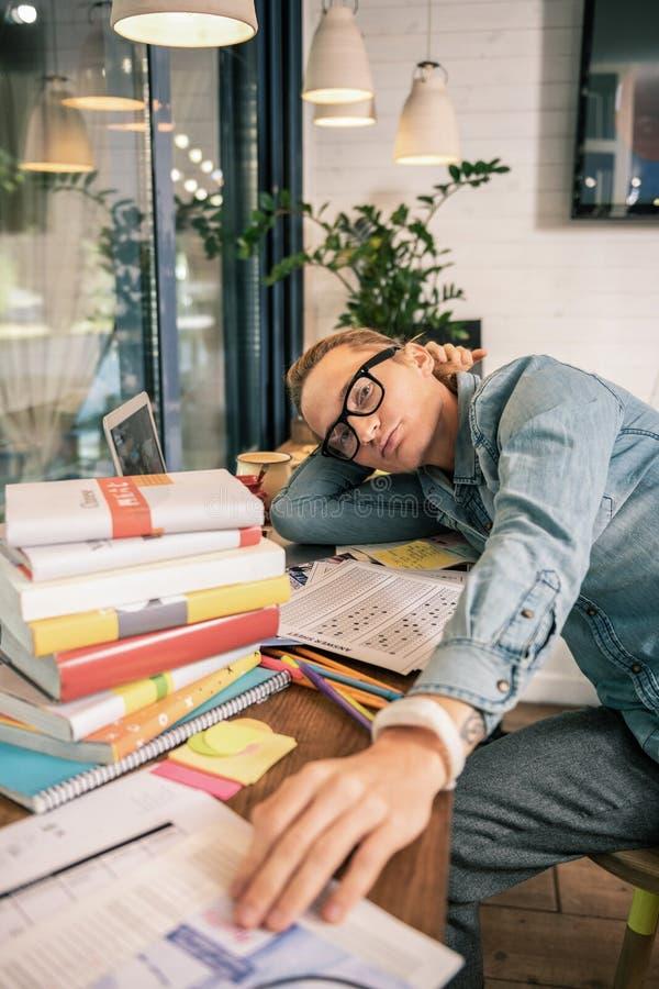 Estudiante joven serio que es rodeado por los libros fotografía de archivo libre de regalías