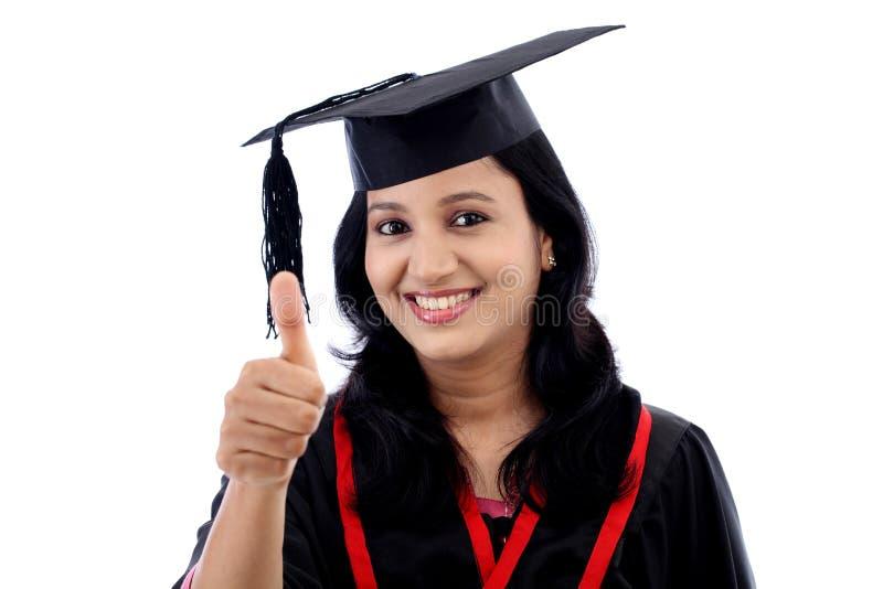 Estudiante joven sonriente de la graduación que hace gesto del thumbsup fotos de archivo