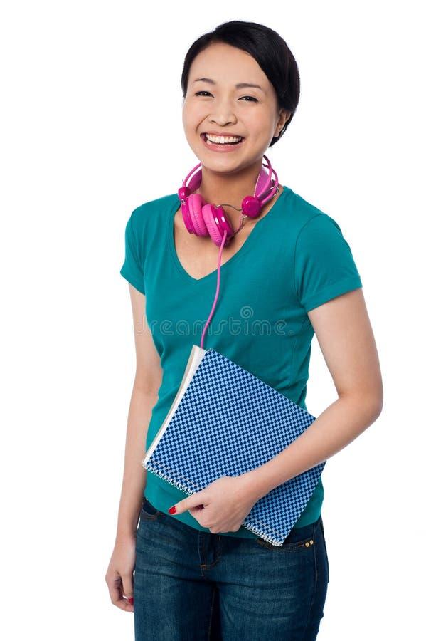 Estudiante joven sonriente que sostiene el cuaderno fotos de archivo libres de regalías